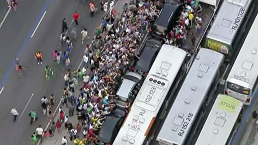 In this image from video, a crowd mobs the silver Fiat carrying Pope Francis, center, through Rio de Janeiro on Monday, July 22, 2013. Ecstatic believers forced the closed Fiat to stop several times as they swarmed around during the drive from the airport to an official opening ceremony in the center of the city. (AP Photo)