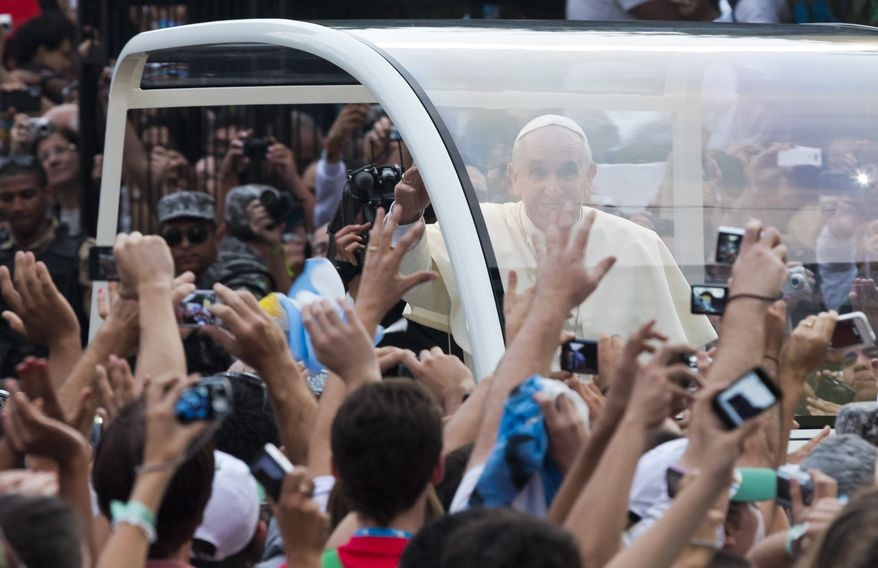 People reach out to Pope Francis as he rides in a popemobile through Rio de Janeiro, Brazil, Monday, July 22, 2013. Pope Francis returned to his home continent for the first time as pontiff, embarking on a seven-day visit meant to fan the fervor of the faithful around the globe. (AP Photo/Domenico Stinellis)