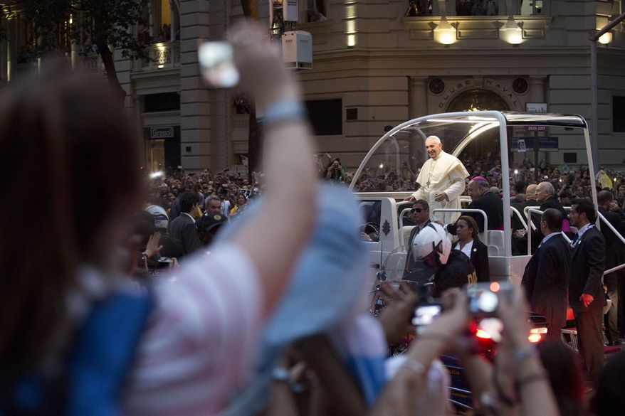 Pope Francis makes his way in a popemobile into central Rio de Janeiro, Brazil, Monday, July 22, 2013. The pontiff arrived for a seven-day visit in Brazil, the world's most populous Roman Catholic nation. During his visit, Francis will meet with legions of young Roman Catholics converging on Rio for the church's World Youth Day festival.(AP Photo/Felipe Dana)