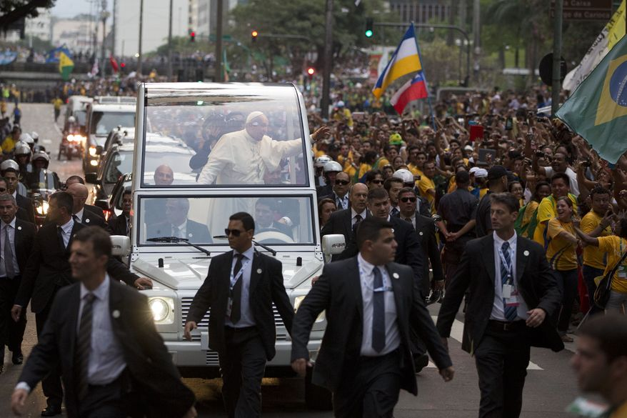 Pope Francis waves from his popemobile as he make his way into central Rio de Janeiro, Brazil, Monday, July 22, 2013. The pontiff arrived for a seven-day visit in Brazil, the world's most populous Roman Catholic nation. During his visit, Francis will meet with legions of young Roman Catholics converging on Rio for the church's World Youth Day festival.(AP Photo/Felipe Dana)