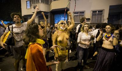 Topless protesters belonging to a gay, lesbian and transgender group, demonstrate near Guanabara Palace in Rio de Janeiro, Brazil on Monday, July 22, 2013. Police and anti-government protesters clashed outside the palace hosting the pope's welcoming ceremony. About an hour after the pope concluded his short speech, police began cracking down on the protests, firing rubber bullets in an effort to disperse the crowd.(AP Photo/Victor R. Caivano)