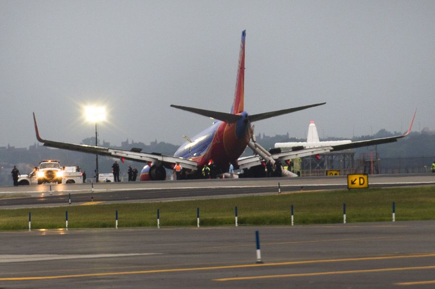 A Southwest Airlines Boeing 737 experienced a collapse of its nose landing gear while touching down at LaGuardia Airport in New York on Monday, July 22, 2013. The plane came to rest on a patch of grass after skidding down the runway. (AP Photo/John Minchillo)