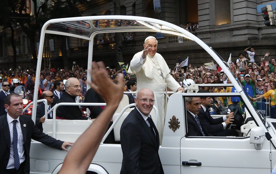 Pope Francis waves from his popemobile as he makes his way into central Rio de Janeiro, Brazil, Monday, July 22, 2013. The pontiff arrived for a seven-day visit in Brazil, the world's most populous Roman Catholic nation. (AP Photo/Victor R. Caivano) **FILE**