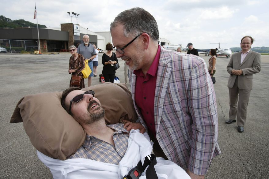 This photo made Thursday, July 11, 2013, shows Jim Obergefell, right, and John Arthur after they returned from their wedding flight at Landmark Aviation at Cincinnati's Lunken Airport. The couple were married during a short ceremony on the plane, on the tarmac, at Baltimore/Washington International Thurgood Marshall Airport, after flying in from Cincinnati. (AP Photo/The Cincinnati Enquirer, Gary Landers)