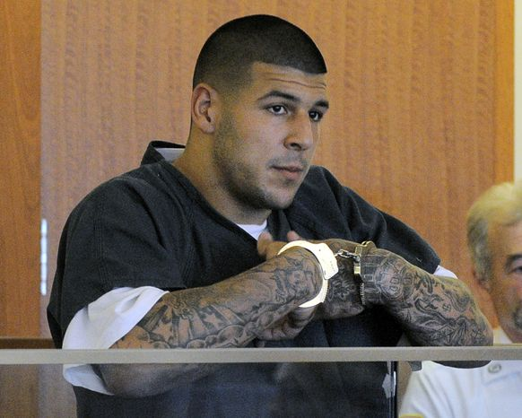 FILE - Former New England Patriots football tight end Aaron Hernandez stands during a bail hearing in Fall River Superior Court in this June 27, 2013 file photo taken in Fall River, Mass. An associate of former New England Patriots tight end Aaron Hernandez said he was told Hernandez fired the shots that resulted in the death of a semi-pro football player, according to documents filed in Florida. The records say Hernandez associate Carlos Ortiz told Massachusetts investigators that another man, Ernest Wallace, said Hernandez shot Lloyd in an industrial park near Hernandez's home in North Attleborough. (AP Photo/Boston Herald, Ted Fitzgerald, Pool)