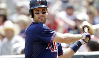 Minnesota Twins' Joe Mauer takes some practice swings on deck in the fourth inning of a baseball game against the Cleveland Indians, Sunday, July 21, 2013 in Minneapolis. (AP Photo/Jim Mone)