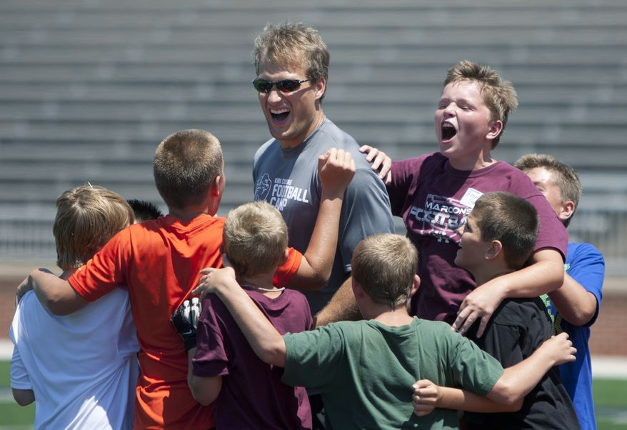 Washington Redskins quarterback Kirk Cousins, middle, motivates students while leading drills during Kirk Cousins Football Camp at Hope College in Holland, Mich., Thursday, July 11, 2013. The camp was open to middle school boys. Cousins played football at Michigan State and at Holland Christian High School. (AP Photo/Grand Rapids Press, Cory Morse)