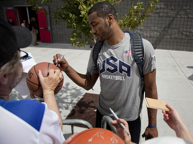 John Wall of the Washington Wizards signs autographs for fans after a USA Basketball mini camp practice, Monday, July 22, 2013, in Las Vegas. Twenty-eight of the best young players in the country are in Las Vegas for four days of workouts that essentially mark the kickoff of 2016 Olympic preparations. (AP Photo/Julie Jacobson)