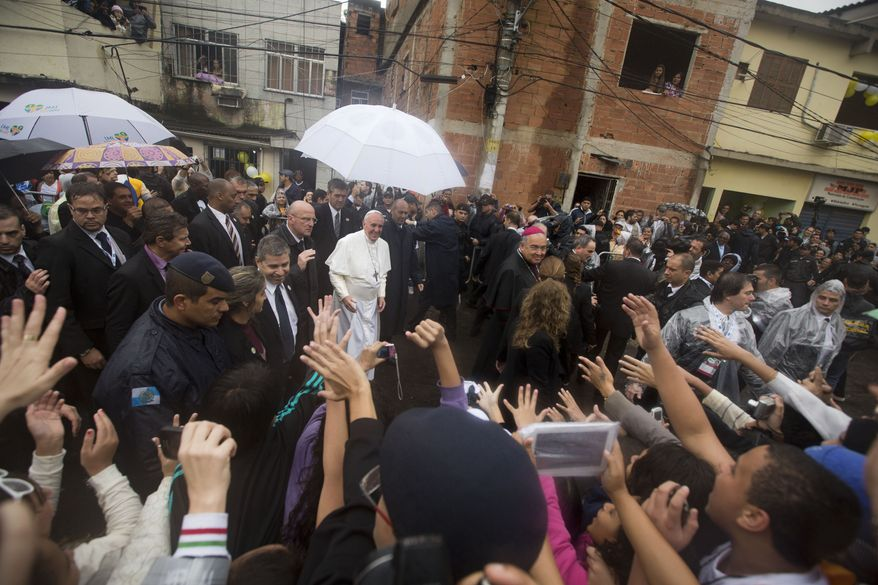 People greet Pope Francis, center, as he visits the Varginha slum in Rio de Janeiro, Brazil, Thursday, July 25, 2013. Francis on Thursday visited one of Rio de Janeiro's shantytowns, or favelas, a place that saw such rough violence in the past that it's known by locals as the Gaza Strip.  (AP Photo/Victor R. Caivano)