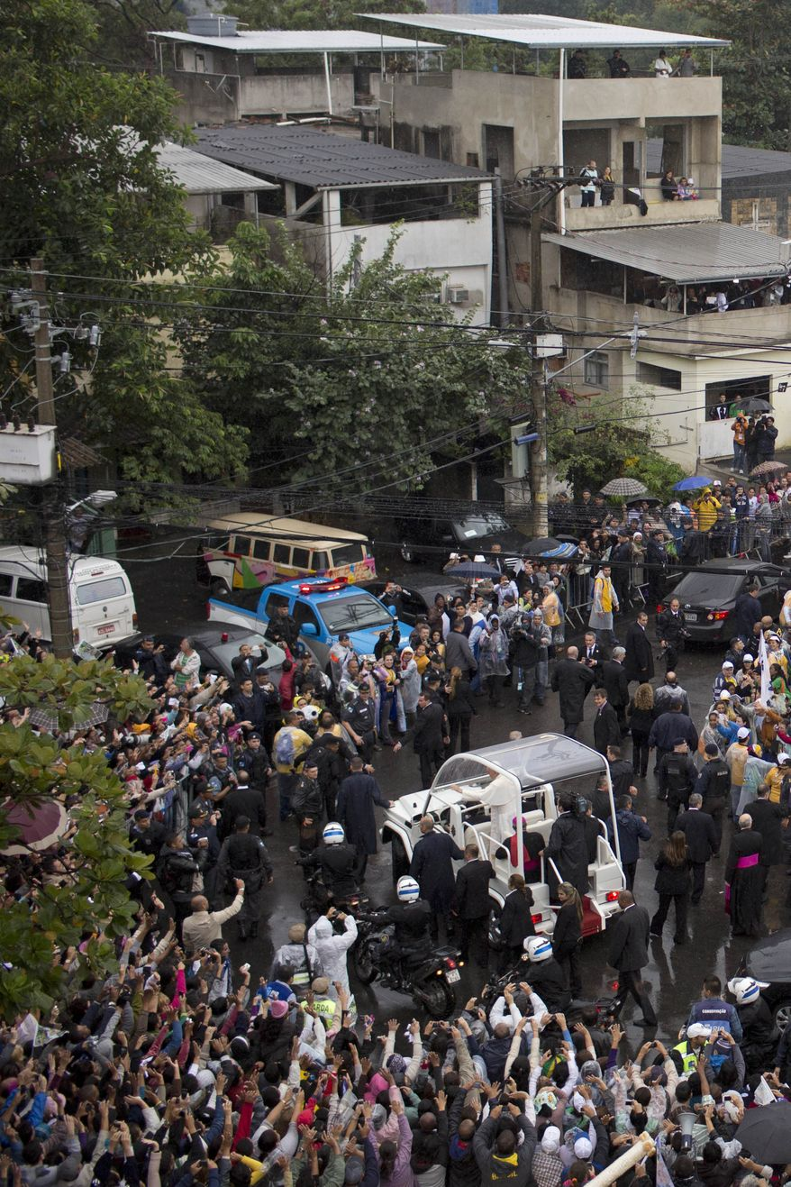 People line the street to greet Pope Francis as he arrives in his popemobile in the Varginha slum, part of the Manguinhos slum complex in Rio de Janeiro, Brazil, Thursday, July 25, 2013. Pope Francis on Thursday visited one of Rio de Janeiro's shantytowns, or favelas, a place that saw such rough violence in the past that it's known by locals as the Gaza Strip. (AP Photo/Felipe Dana)