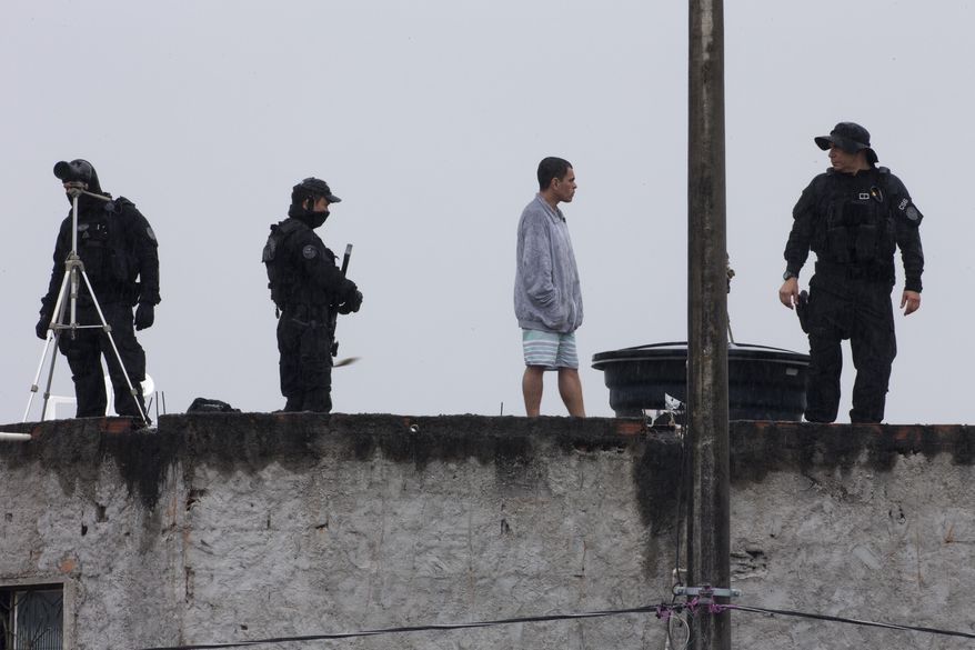 Security forces stand on a roof in the Varginha slum soon before the arrival of Pope Francis in Rio de Janeiro, Thursday, July 25, 2013. Francis on Thursday visited one of Rio de Janeiro's shantytowns, or favelas, a place that saw such rough violence in the past that it's known by locals as the Gaza Strip.  (AP Photo/Domenico Stinellis)