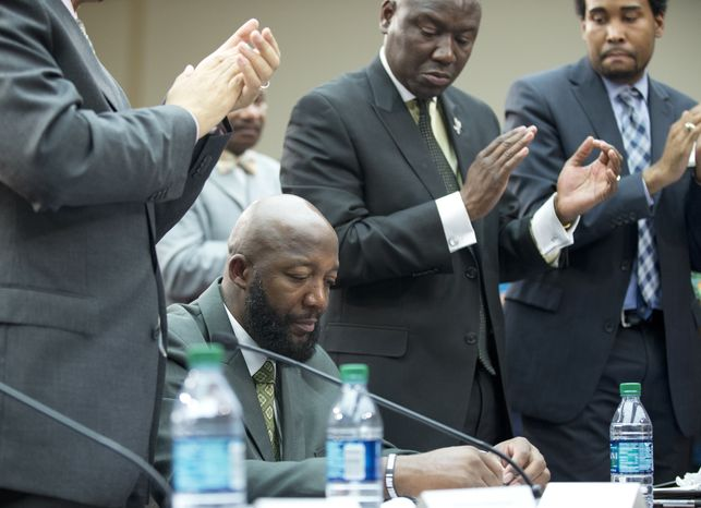 """Tracy Martin, bottom, the father of slain 17-year old Trayvon Martin, looks down as the crowd give him an applause during a forum titled """"The Status of Black Males: Ensuring Our Boys Mature Into Strong Men"""" on Capitol Hill Washington, Wednesday, July 24, 2013. (AP Photo/Manuel Balce Ceneta)"""