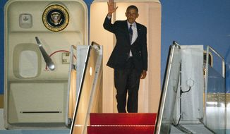 President Barack Obama waves as he exits Air Force One at Andrews Air Force Base, Md., Wednesday, July 24, 2013. (AP Photo/Cliff Owen)