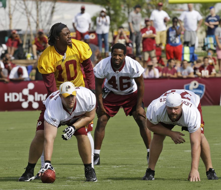 Washington Redskins quarterback Robert Griffin III (10) looks over the line as he gets ready to take a snap from center, Will Montgomery bottom left, as Korey Lichtensteiger, right, and running back Alfred Morris (46) begin their training camp at the NFL football teams new practice facility in Richmond, Va. Thursday, July 25, 2013. (AP Photo/Steve Helber)