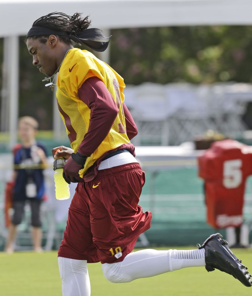 Washington Redskins quarterback Robert Griffin III runs to the practice field as the team begins their training camp at the NFL football teams new practice facility in Richmond, Va. Thursday, July 25, 2013. (AP Photo/Steve Helber)
