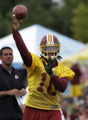 Washington Redskins quarterback Robert Griffin III tosses a pass during NFL football training camp in Richmond, Va. Thursday, July 25, 2013. (AP Photo/Steve Helber)