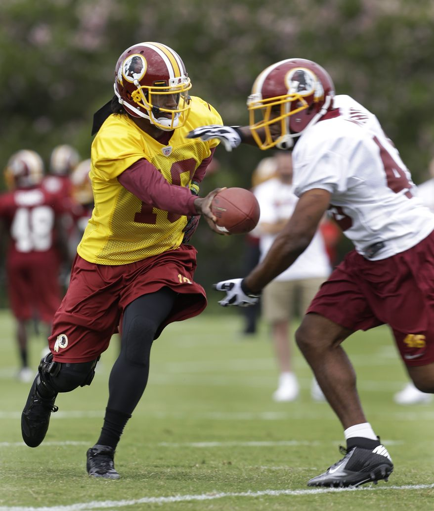 Washington Redskins quarterback Robert Griffin III, left, hands the ball off to Alfred Morris, right, during NFL football training camp in Richmond, Va. Thursday, July 25, 2013. (AP Photo/Steve Helber)