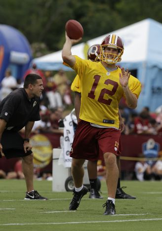Washington Redskins quarterback Kirk Cousins (12) tosses a pass as the team begins their training camp at the new NFL teams practice facility in Richmond, Va. Thursday, July 25, 2013. (AP Photo/Steve Helber)
