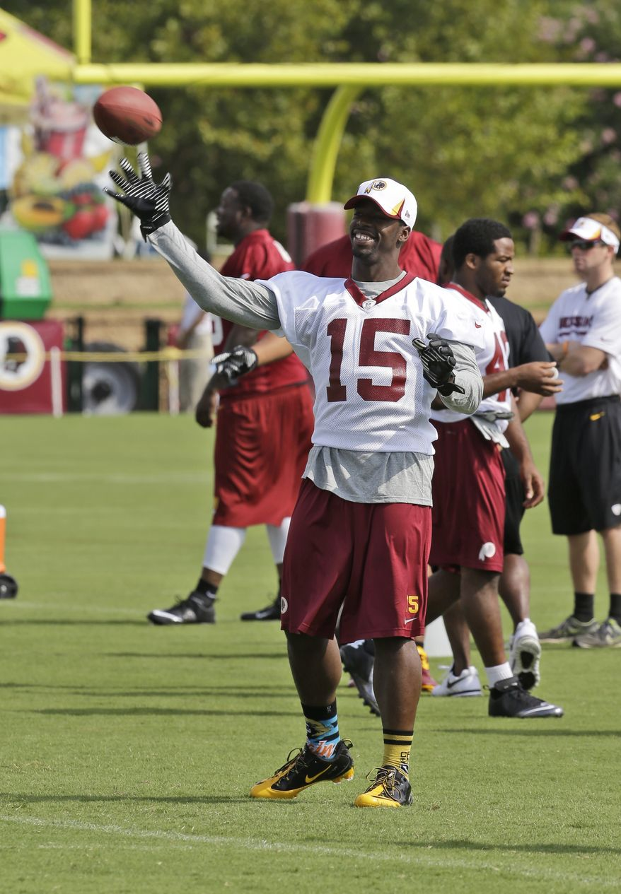 Washington Redskins Washington Redskins wide receiver Josh Morgan (15) tosses the ball as they begin their training camp at the NFL football teams new practice facility in Richmond, Va. Thursday, July 25, 2013. (AP Photo/Steve Helber)