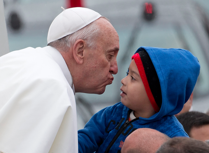 Pope Francis reaches out to kiss a child as he arrives to the Aparecida Basilicia in Aparecida, Brazil, Wednesday, July 24, 2013.  (AP Photo/Domenico Stinellis)