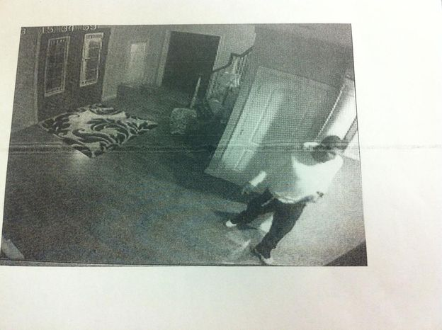 Aaron Hernandez captured on his on home surveillance video carrying what appears to be a handgun. (credit: Attleboro District Court)