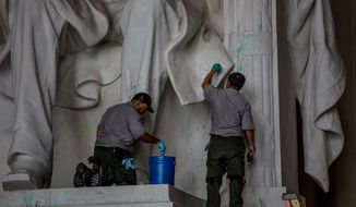 National Park Service employees use cleaning supplies in an effort to remove green paint that was used to vandalize the Lincoln Memorial, in Washington, DC., Friday, July 26, 2013. (Andrew S. Geraci/The Washington Times)