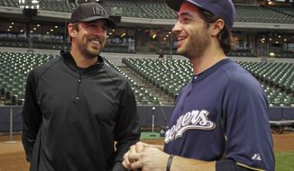 "FILE - In this June 9, 2011 file photo, Green Bay Packers NFL football quarterback Aaron Rodgers, left, and Milwaukee Brewers outfielder Ryan Braun speak during batting practice before a baseball game between the Brewers and the New York Mets,, in Milwaukee. Rodgers says he was ""shocked"" when his friend Ryan Braun admitted he violated baseball's rules against using performance-enhancing substances. (AP Photo/Jeffrey Phelps, File)"