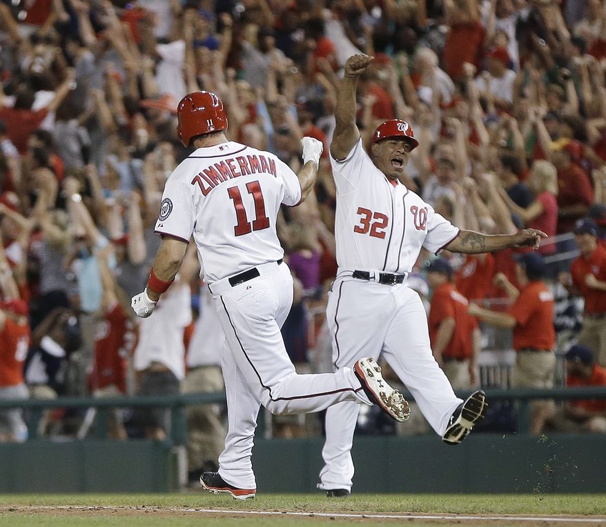 Washington Nationals third baseman Ryan Zimmerman celebrates his walk-off home run against the New York Mets with first base coach Tony Tarasco. (Associated Press photo)