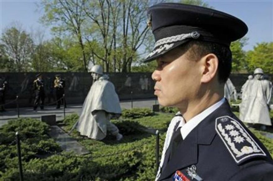 ** FILE ** A member of the South Korean military stands at attention at the Korean War Memorial in Washington, April 12, 2010. President Obama is marking the 60th anniversary of the end of the Korean War. Obama is making remarks Saturday at a commemorative ceremony at the Korean War Veterans Memorial on the National Mall. (Associated Press)