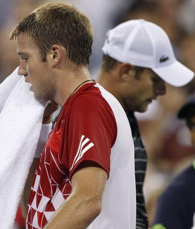 **FILE** Jack Sock, left, of Lincoln, Neb., passes Andy Roddick, right, of Omaha, Neb., during their match at the U.S. Open tennis tournament in New York, Friday, Sept. 2, 2011. (AP Photo/Charles Krupa)
