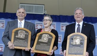 Family representatives Jerry Watkins, left, great grandson of Baseball Hall of Fame inductee Deacon White, Anne Vernon, center, great grandniece of inductee Jacob Ruppert, and Dennis McNamara, grandnephew of inductee Hank O'Day, hold the players' plaques after a ceremony on Sunday, July 28, 2013, in Cooperstown, N.Y. (AP Photo/Mike Groll)