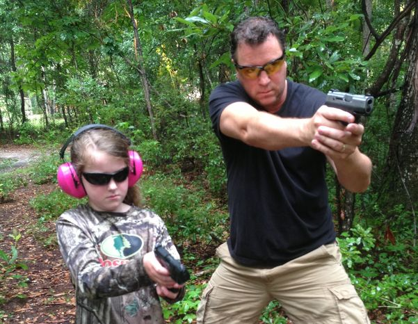 Scott Ose teaching his daughter Zoe how to shoot with a handgun. Photo courtesy of the Ose family.