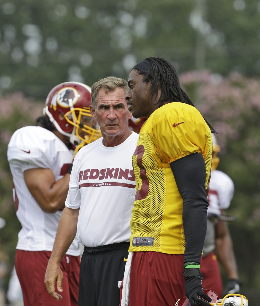 Washington Redskins quarterback Robert Griffin III, right, talks with head coach Mike Shanahan, during the NFL football teams training camp in Richmond, Va. Saturday, July 27, 2013. (AP Photo/Steve Helber)