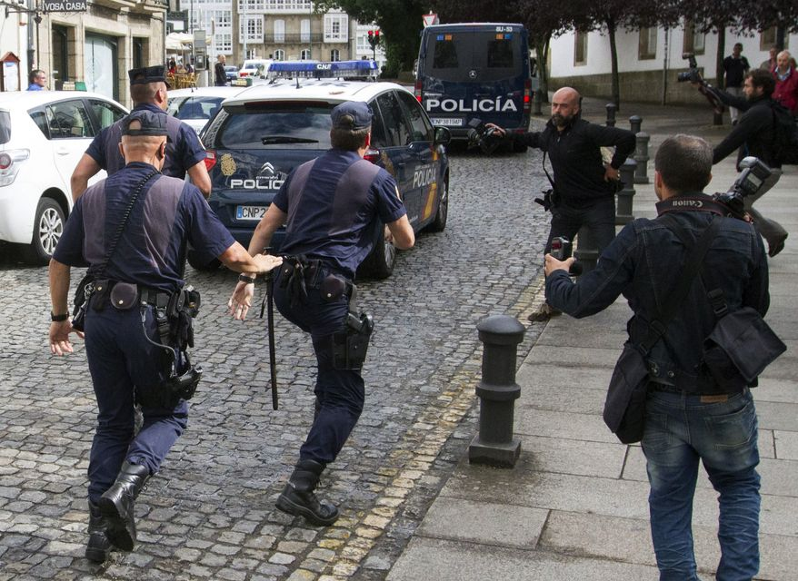 Members of the media, with police in pursuit, run after a police car carrying arrested train driver Francisco Jose Garzon Amo (unseen) to testify in court in Santiago de Compostela, Spain, on Sunday, July 28, 2013. (AP Photo/Lalo R. Villar)