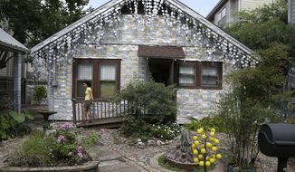 A visitor leaves the back entrance to the beer can house, a Houston landmark, Wednesday, July 10, 2013. Former owner John Milkovisch covered the outside on the house with siding made of cut and flatten beer cans and garlands made from the lids. (AP Photo/Pat Sullivan)