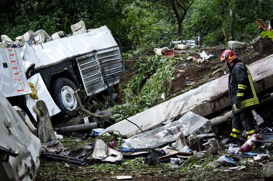 A firefighter walks amongst the the wreckage of a bus and a blood-stained guardrail hours after the bush crashed off a highway near Avellino, southern Italy, Monday, July 29, 2013. (AP Photo/Salvatore Laporta)