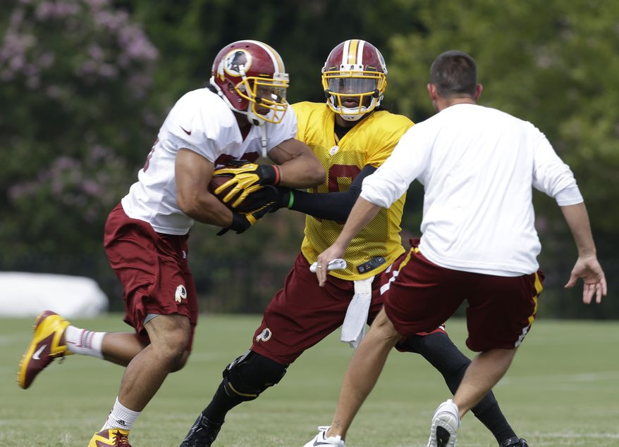 Washington Redskins quarterback Robert Griffin III, center hands the ball off to running back Roy Helu, left, as offensive coordinator Kyle Shanahan closes in during the NFL football teams training camp in Richmond, Va. Saturday, July 27, 2013. (AP Photo/Steve Helber)