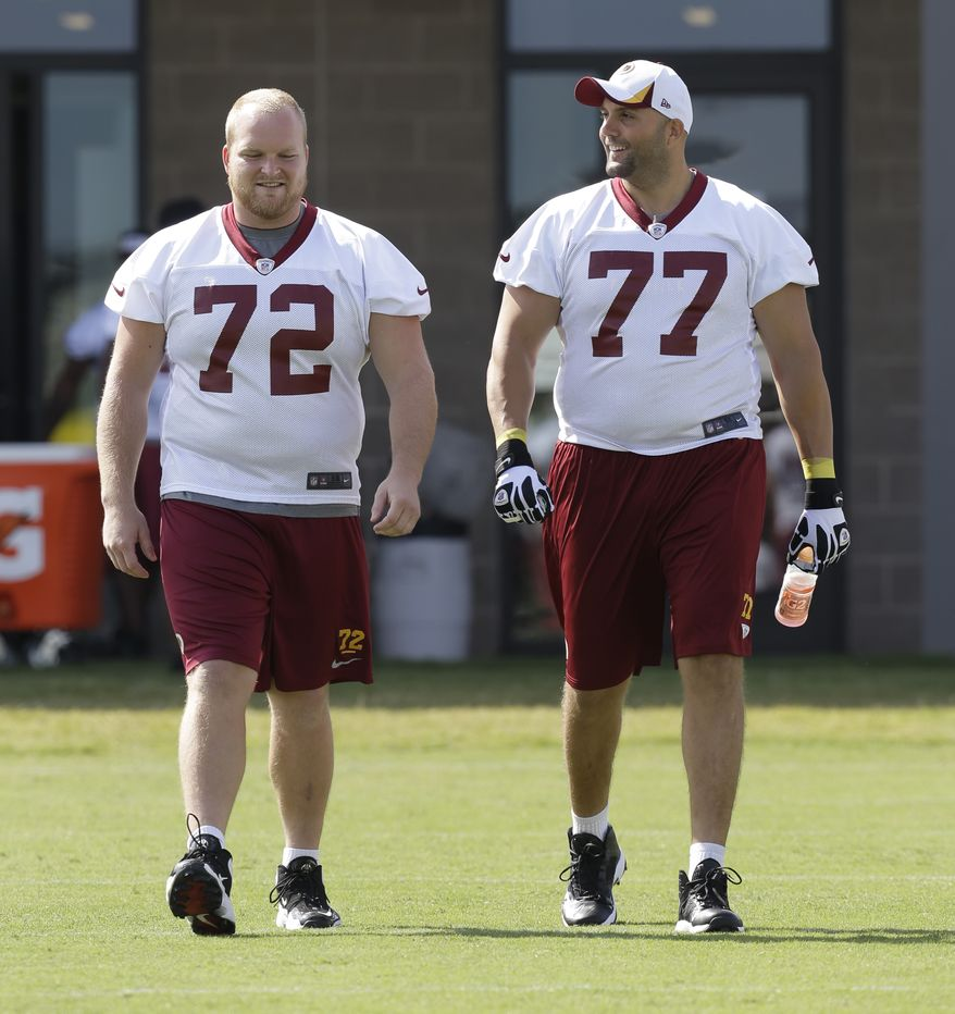 Washington Redskins center Kevin Matthews (72) and Washington Redskins tackle Tony Pashos (77) walk to the field during the second day of the NFL football teams training camp in Richmond, Va. Friday, July 26, 2013. (AP Photo/Steve Helber)