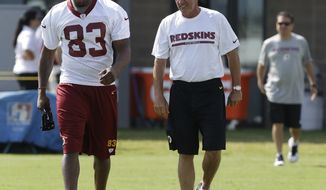 Washington Redskins tight end Fred Davis (83) walks with head coach Mike Shanahan, right, during the second day of the NFL football teams training camp in Richmond, Va. Friday, July 26, 2013. (AP Photo/Steve Helber)