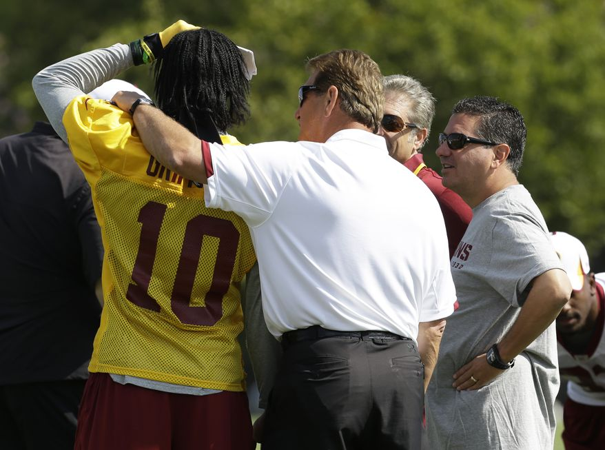 Former Washington Redskin quarterback Joe Theismann puts his arm around Redskins quarterback Robert Griffin III (10) as owner Daniel Snyder, right looks on during the second day of the NFL football teams training camp in Richmond, Va. Friday, July 26, 2013. (AP Photo/Steve Helber)