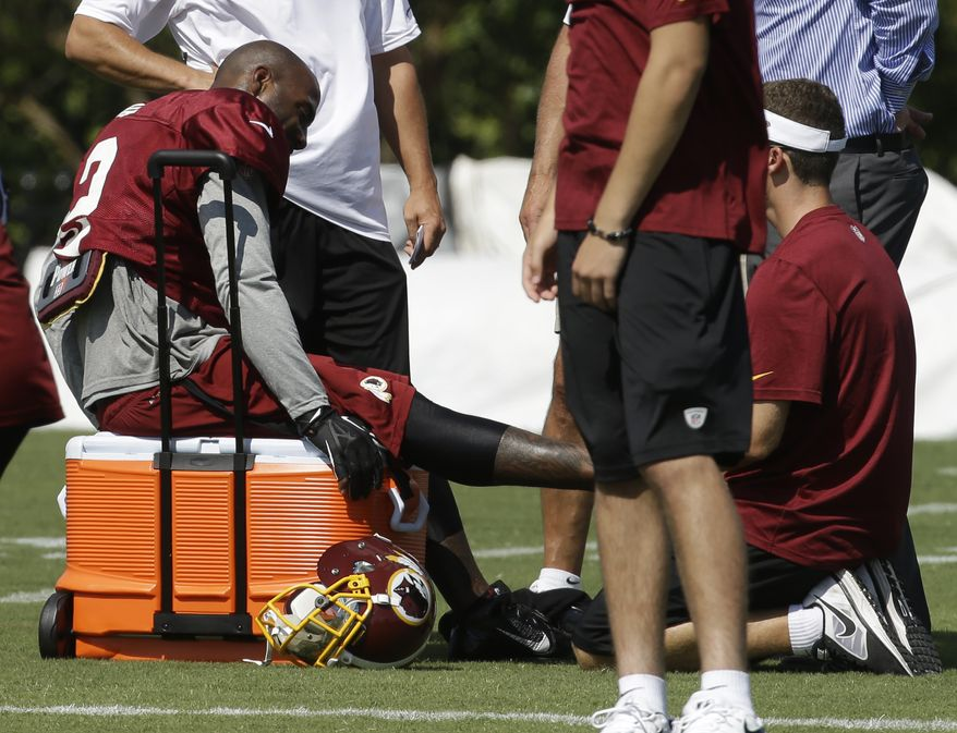Washington Redskins cornerback DeAngelo Hall, left, gets attention on the sidelines during the afternoon practice at the NFL football teams training camp in Richmond, Va. Monday, July 29, 2013. (AP Photo/Steve Helber)