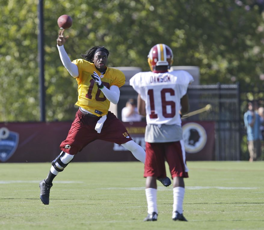 Washington Redskins quarterback Robert Griffin III (10) tosses the ball to wide receiver Skye Dawson (16) during the afternoon practice at the NFL football teams training camp in Richmond, Va. Monday, July 29, 2013. (AP Photo/Steve Helber)