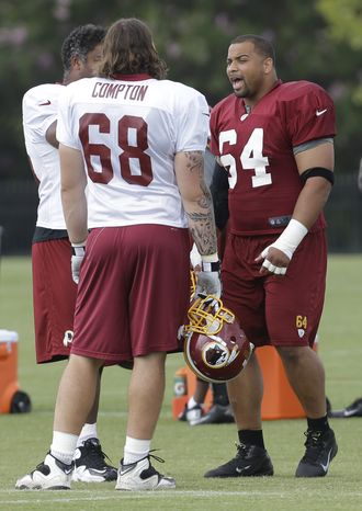Washington Redskins defensive tackle Kedric Golston (64) talks with teammate, tackle Tom Compton (68) during the NFL football teams training camp in Richmond, Va. Saturday, July 27, 2013. Golston is now tied for second in seniority on the Washington Redskins and now he gets another chance to start because of Jarvis Jenkins' drugs suspension. (AP Photo/Steve Helber)