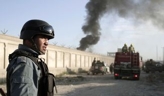 **FILE** An Afghan security force member stands guard near the entrance gate of a NATO compound following a suicide bombing in Kabul, Afghanistan, on July 2, 2013. Militants blew up a suicide car bomb at the gate to the compound and attacked guards with small-arms fire, killing four guards and two civilians, police said. All four suicide attackers were also killed. (Associated Press)