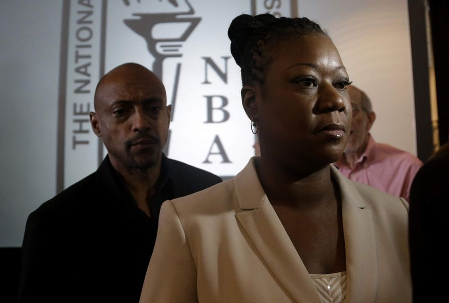 Sybrina Fulton, mother of slain teenager Trayvon Martin, leaves a news conference held by the National Bar Association where they addressed what they say are inequalities in the U.S. justice system related to gun violence and African-Americans, Monday, July 29, 2013, in Miami Beach, Fla. (AP Photo/Lynne Sladky)