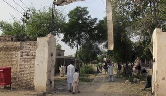 A plainclothes police officer takes a photo with his mobile phone of a jail gate that was damaged when Taliban militants attacked, Tuesday, July 30, 2013, in Dera Ismail Khan, Pakistan. (AP Photo/Ishtiaq Mahsud)