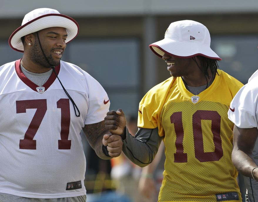 Washington Redskins tackle Trent Williams (71) and quarterback Robert Griffin III (10) walk out for the morning practice at the NFL football teams training camp in Richmond, Va. Tuesday, July 30, 2013. (AP Photo/Steve Helber)