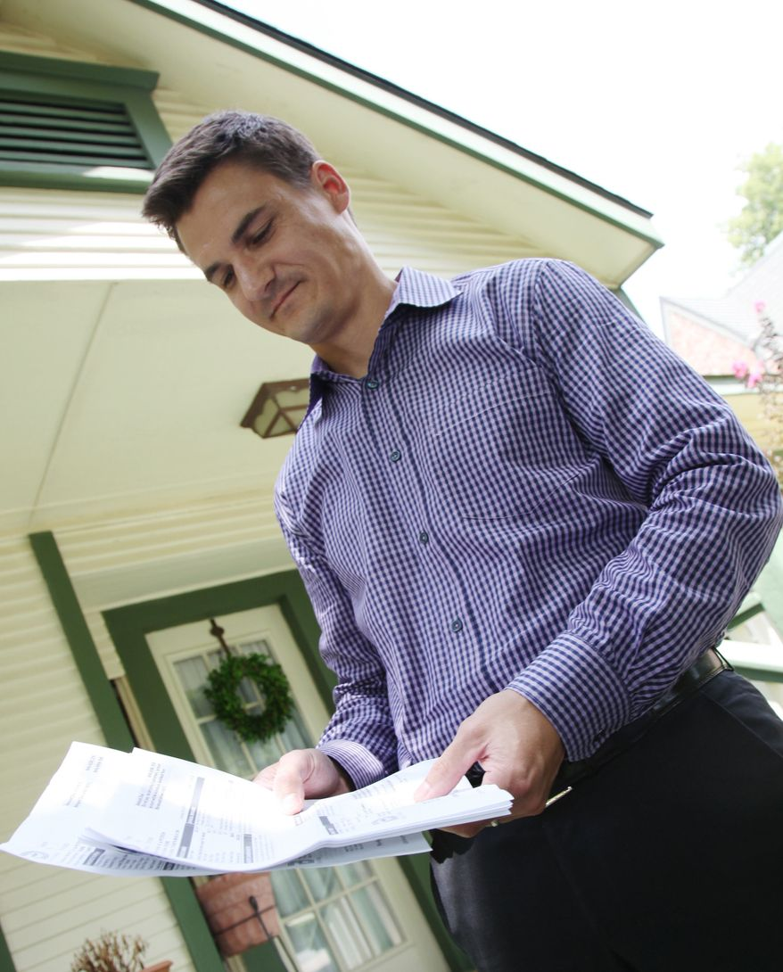 Tom Hoffman holds his water bill from the City of Dallas on Tuesday, July 30, 2013, in Dallas. He says he's shocked to have been swamped with a nearly $67,000 erroneous water bill a few months after a similar error. Dallas officials blame the mishap on a bad water meter. (AP Photo/John L. Mone)