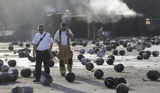 Firefighters walk through an area of exploded propane cylinders in the aftermath of an explosion and fire at a propane gas company, Tuesday, July 30, 2013, in Tavares, Fla. (AP Photo/John Raoux)