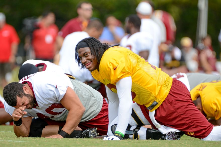 Washington Redskins quarterback Robert Griffin III (10) laughs during stretches before afternoon practice at the Bon Secours Washington Redskins Training Center, Richmond, Va., Tuesday, July 30, 2013. (Andrew Harnik/The Washington Times)